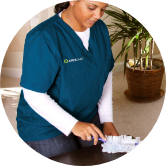 ApexCare caregiver assisting in cleaning a client's home.