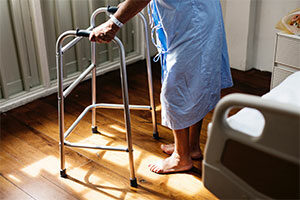 Photo of a senior hospital patient using a walker for assistance.