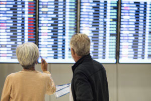 Man and woman checking flight times board while travelling.